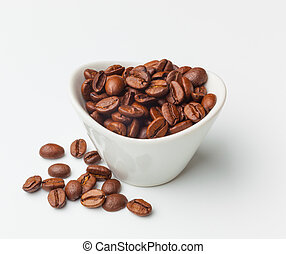 A bowl of roasted coffee beans isolated on white