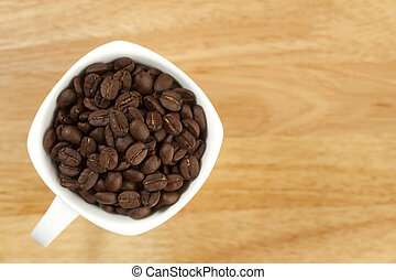 Coffee beans in a cup on wooden background