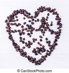Coffee beans in a form of a heart on a white wooden background