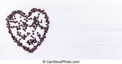 Coffee beans in a form of a heart on a white wooden background with a space for your text