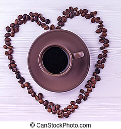 Coffee beans in a form of a heart with a cup of coffee on a white wooden background