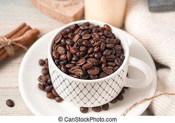 Coffee beans in a mug close-up on a light background.