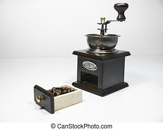 Coffee beans in a small box of wooden coffee grinder on white background
