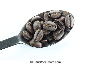 Coffee beans in a stainless steel spoon.