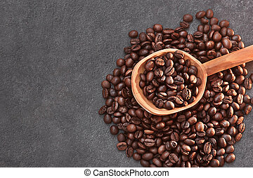 Coffee beans in a wooden spoon on dark background