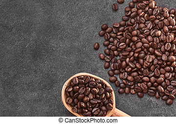 Coffee beans in an old wooden spoon