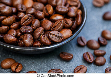 Coffee beans in black bowl on grey slate background. Close up.