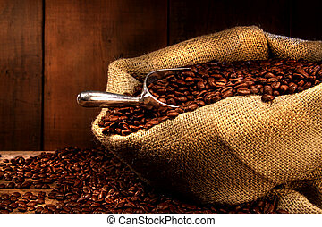 Coffee beans in burlap sack with antique wood background