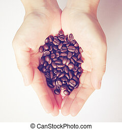 Coffee beans in hands with retro filter effect