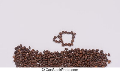 Coffee beans in shape of cup and smiley face - Pile of...
