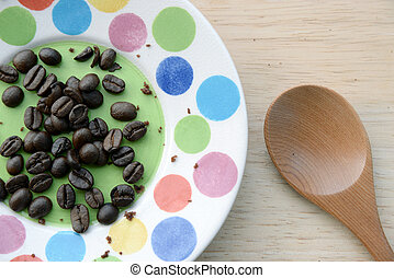 coffee beans in small plate and ground coffee in wooden spoon