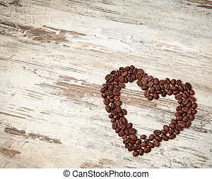 coffee beans in the form of heart on a wooden table