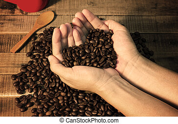 Coffee beans in the hand of a woman show love