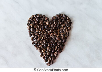 Coffee beans in the shape of heart on a white background