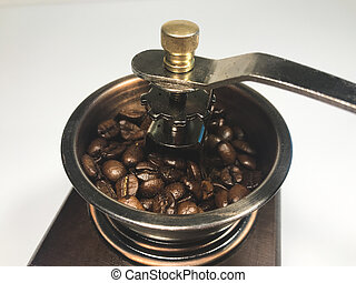 Coffee beans in the wooden coffee grinder on white background. Close-up