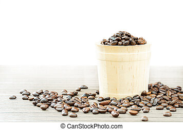 Coffee beans in wood bucket on wooden floor close up