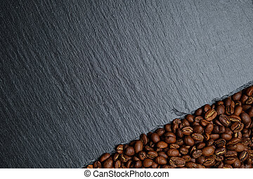Coffee beans next to the slate board. Top view. Copy space.