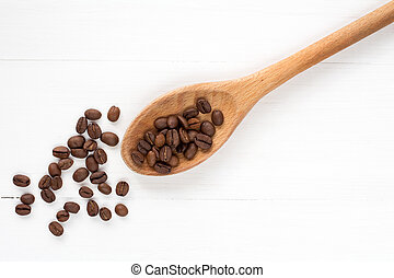 Coffee beans on a spoon and wooden background