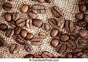 Coffee beans on burlap sack background