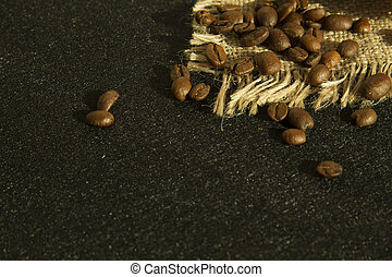 Coffee beans on the linen cloth and black background