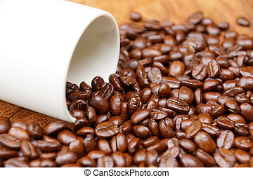 Coffee beans on the wooden background.