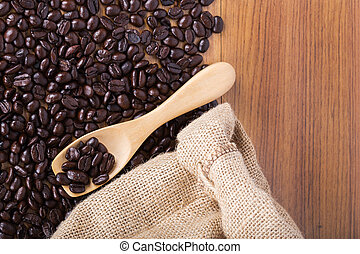 coffee beans on wooden spoon with burlap on table