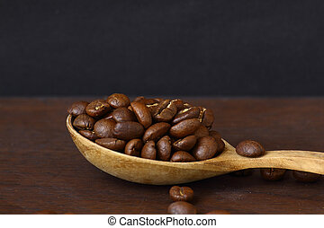 Coffee beans on wooden spoon with grunge background