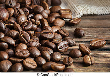 Coffee beans on wooden surface. Closeup. Copy space.