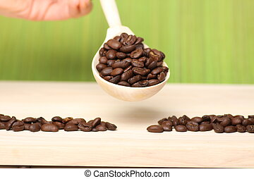 coffee beans on wooden table with spoon