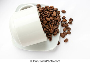 coffee beans spilled out of a cup isolated on white background.