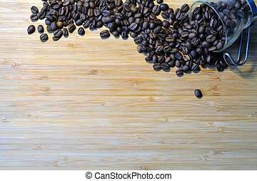 coffee beans spilled out of a glass cup