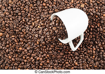 Coffee beans spilled out of cup