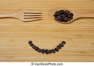 Coffee beans, spoon and fork on wooden background