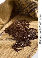 Coffee Beans - Roasted Coffee beans lying on top of a brown...