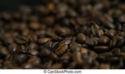 Coffee beans strewing onto the black background from the top