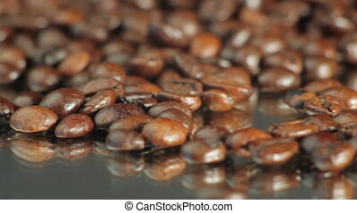 Coffee beans - Roasted coffee beans rotates on the table....