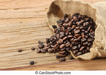 Coffee beans with burlap sack on wood background