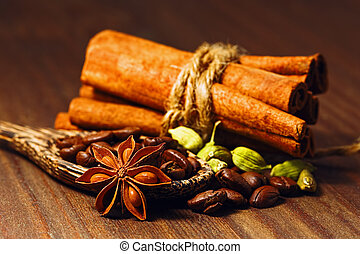 Coffee beans with spices in the wooden spoon