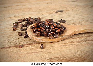 Coffee beans with spoon on wooden table