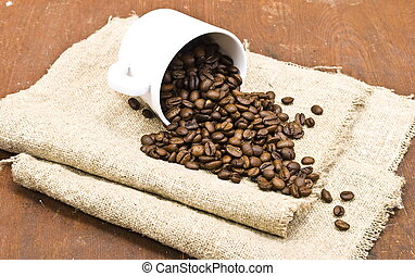 Coffee beans with white cup on sackcloth
