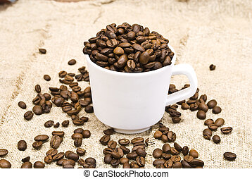Coffee beans with white cup on sack