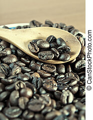 Coffee beans with wooden spoon close-up