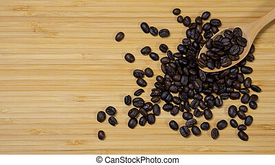 Coffee beans with wooden spoon on wood table