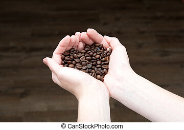 Coffee beans, woman showing medium roasted coffee beans handful