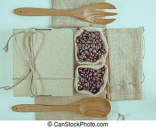 Coffee beans wooden spoon and fork on sack surface. Filter effect retro vintage style