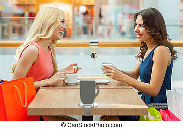 Coffee break after shopping. Two beautiful young women having coffee at restaurant