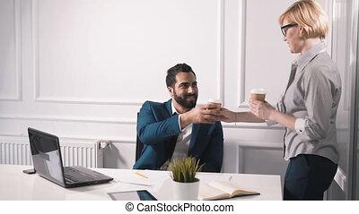 Coffee Break at Work - Two colleagues having tasty hot...