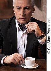 Coffee break. Confident mature businessman looking at camera while sitting with a cup of coffee in his hand