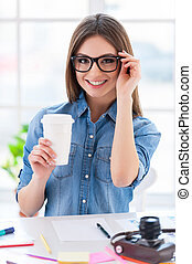 Coffee break. Confident young business woman sitting at her working place and drinking coffee