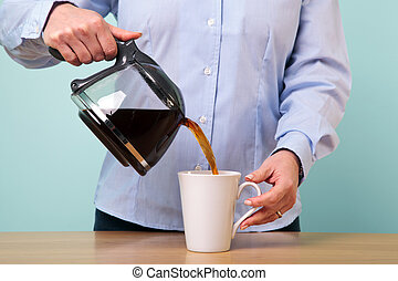 Photo of a woman on her break pouring herself a mug of hot filtered coffee from a glass pot.